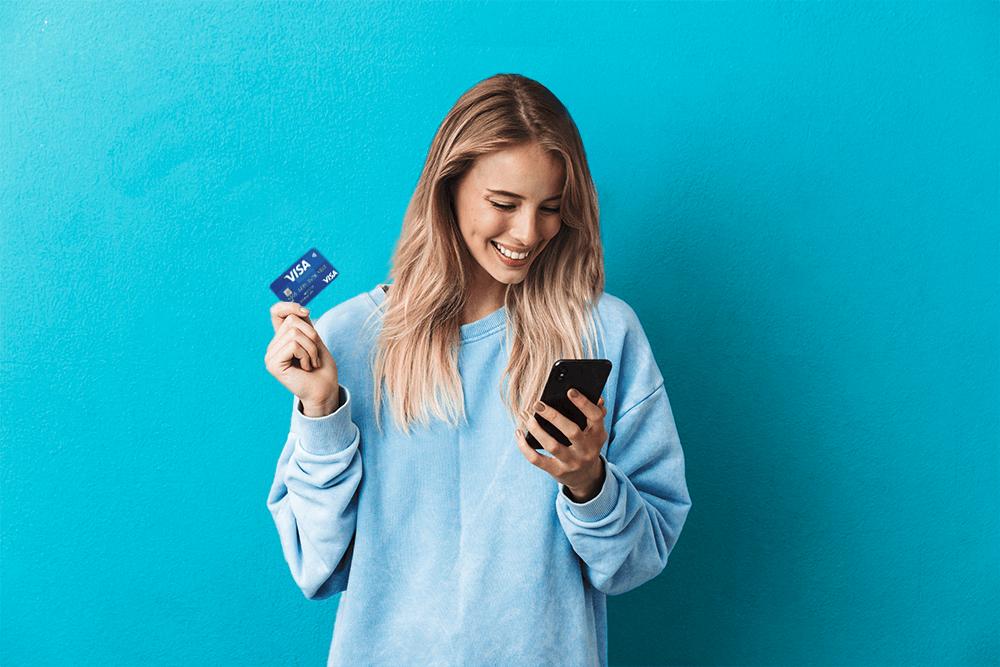 młoda, uśmiechnięta blond kobieta ubrana w niebieską bluzę, trzymająca kartę płatniczą w prawej ręce i telefon w lewej ręce